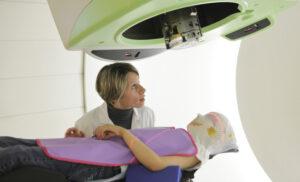 Mise en place du masque de contention et positionnement de l'enfant pour une séance de traitement par protonthérapie. Avec les protons, les radiothérapeutes disposent d'un rayonnement à la balistique ultra-précise, fort utile quand il s'agit de traiter des tumeurs à proximité d'organes sensibles et tout particulièrement chez les enfants. La protonthérapie permet également de réduire le risque de deuxième cancer.